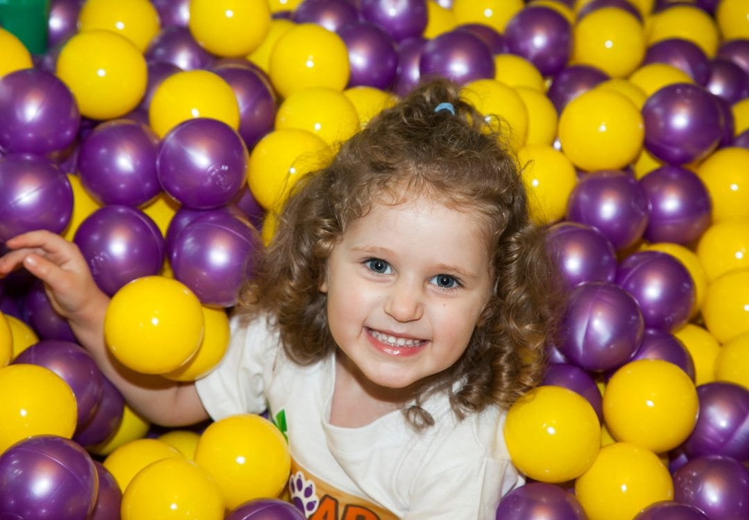 young girl in ball pit smiling