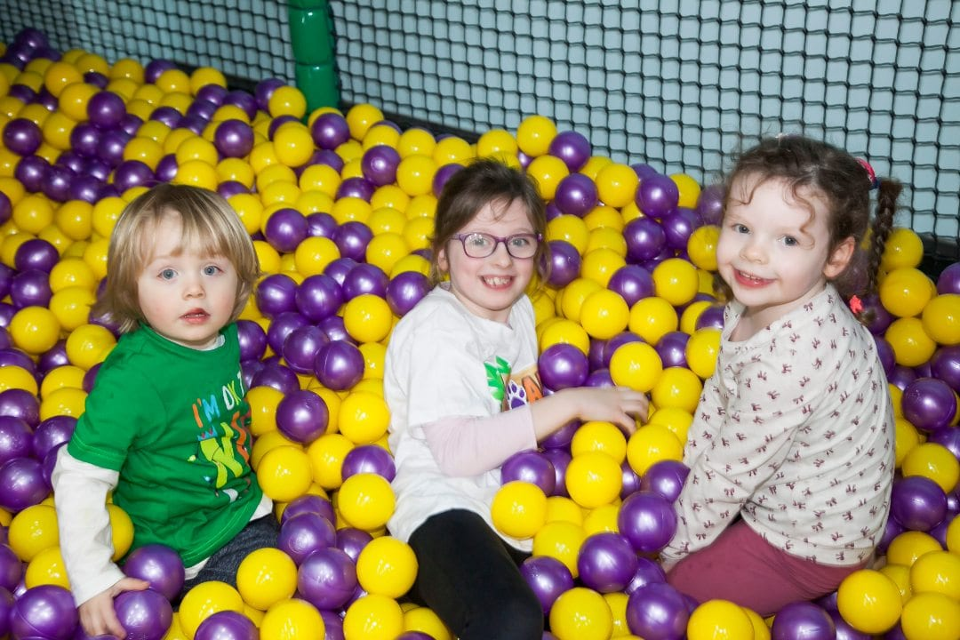three girls at roar and explore enjoying their time in the ball pit